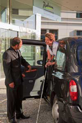Visually impaired guest guided by porter from black cab